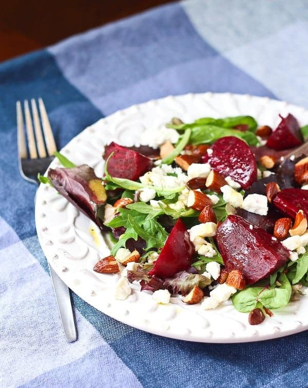 Partial image of salad on plate with fork.