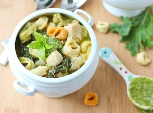 Overhead of chicken tortellini soup in decorative white bowl.