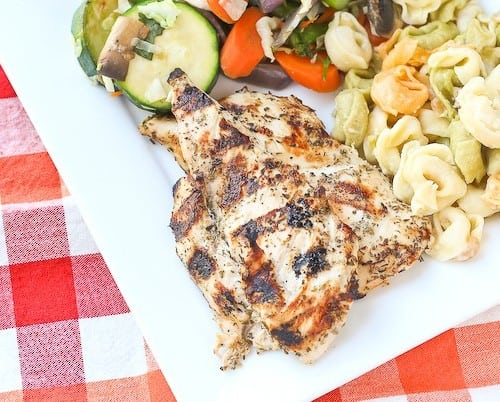 Partial overhead of plated grilled chicken dinner with vegetables and pasta.