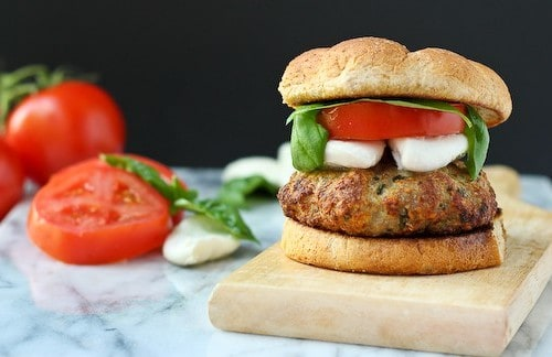 Front view of burger on bun with more mozzarella, tomato slice, and basil leaves.