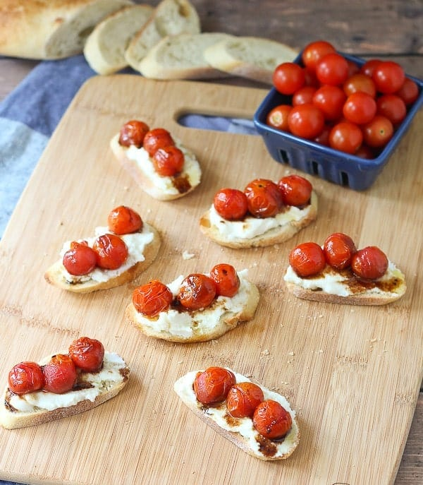 Overhead of several crostini arranged on cutting board, with container of fresh cherry tomatoes and sliced bread.