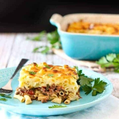 Front view of plated pastitsio with casserole dish in background.