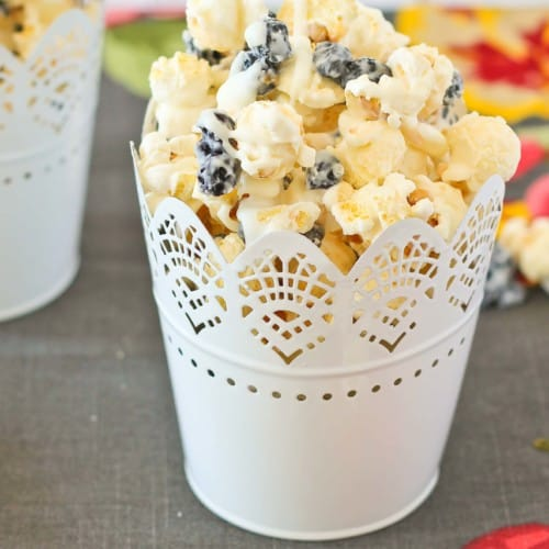 A serving of popcorn in a white lacy decorative tin.