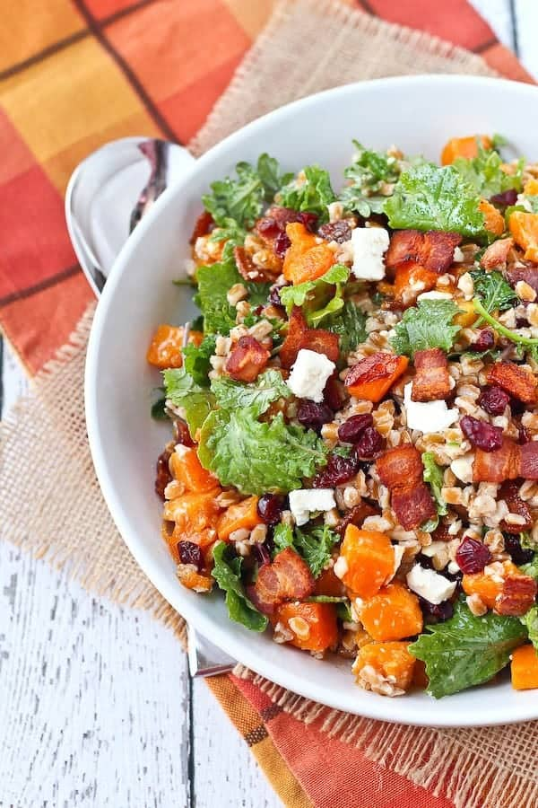 Partial overhead image of white round bowl containing Farro Salad with Butternut Squash, Bacon, Cranberries, Kale and Feta.