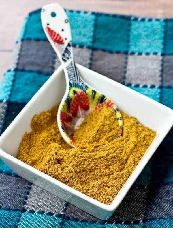 Spice mixture in white square bowl, with decorative spoon, on blue plaid cloth.