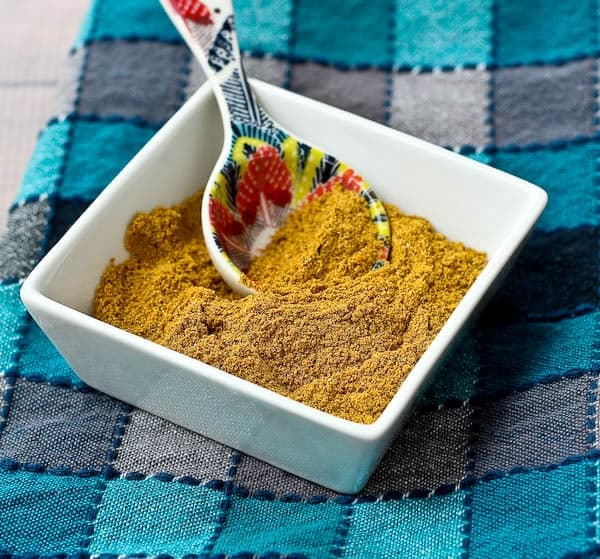 Overhead of curry spice mixture in square bowl, on blue plaid cloth.