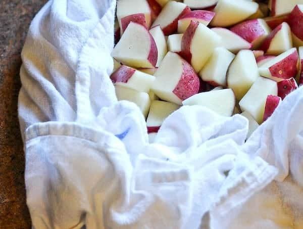 Closeup of diced raw potatoes wrapped in white dish towel.
