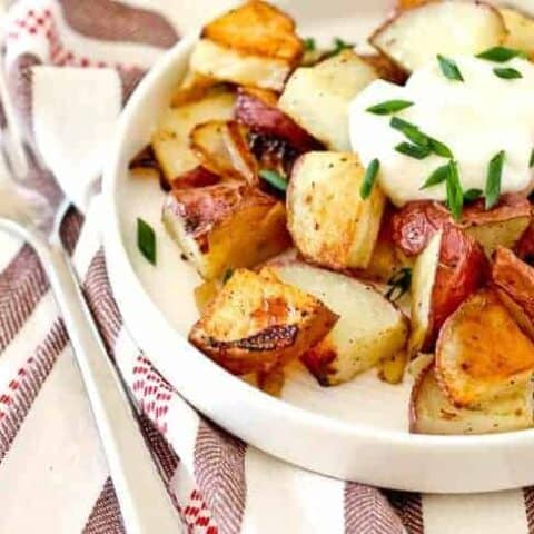 Closeup front view of shallow white bowl containing crispy roasted potatoes garnished with sour cream and chives.