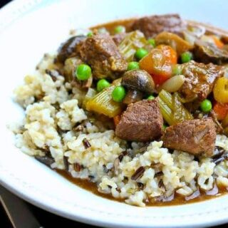 Beef stew in shallow white dish served with white rice.