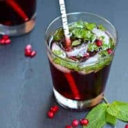 Front top view of pomegranate mojito in clear glass tumbler with white birch straw.