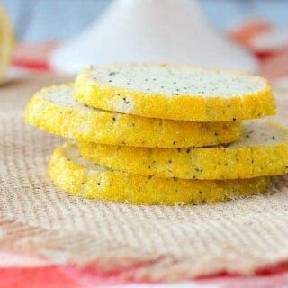 Front view of four poppy seed cookies stacked on burlap cloth.