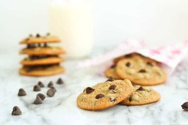 Malt chocolate chip cookies with additional cookies in background along with a glass of milk.