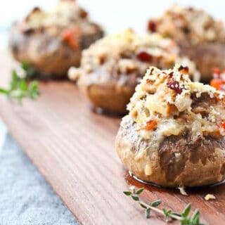 Several stuffed mushrooms on wooden surface, with thyme sprigs.