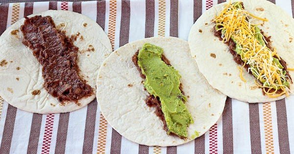 Three open face tortillas spread with black beans, guacamole, and sprinkled with cheese.