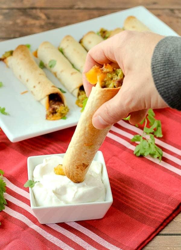 Taquito grasped in hand, dipping into small dish of sour cream.