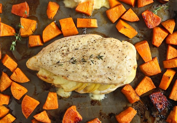 Overhead of a chicken. breast on sheet pan with sweet potatoes.