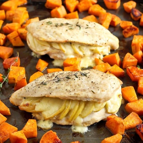 Two stuffed chicken breasts on sheet pan with sweet potatoes.