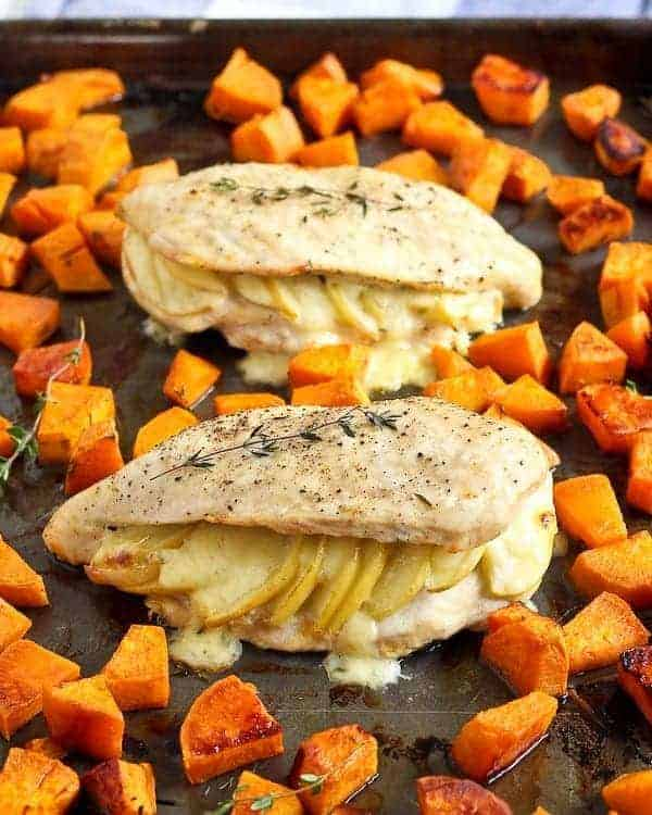 Two stuffed chicken breasts on sheet pan with roasted sweet potatoes.