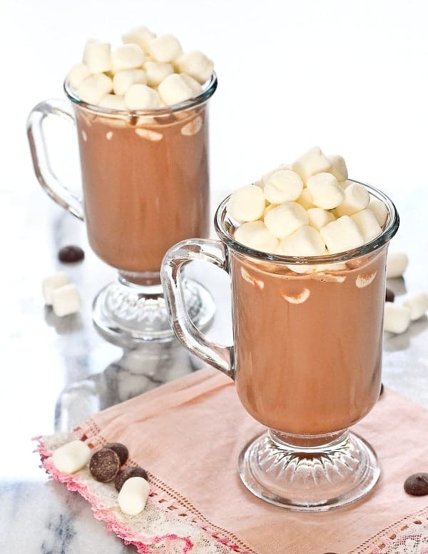Two footed glass mugs of hot chocolate loaded with mounds of mini marshmallows.