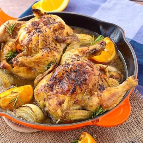 Two cornish hens in an orange skillet garnished with orange wedges and fresh rosemary.