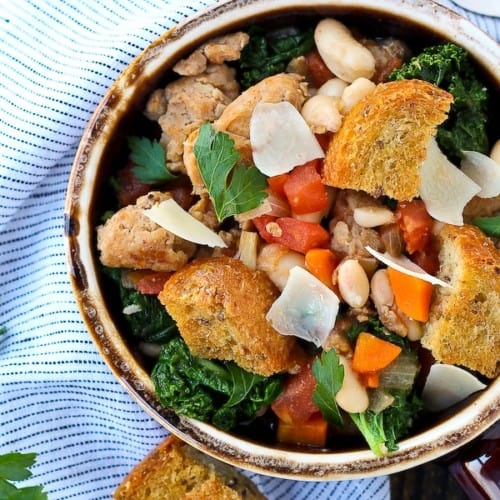 Overhead of earthenware bowl containing sausage, bean, and kale soup garnished with large croutons.