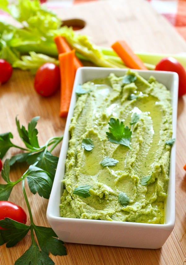 White rectangular serving dish with hummus, garnished with parsley leaves, surrounded by fresh veggies.