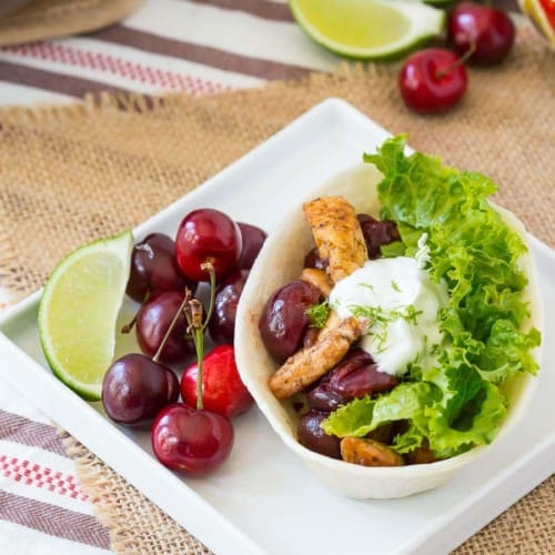 Taco plate on white plate with cherries and wedge of lime.