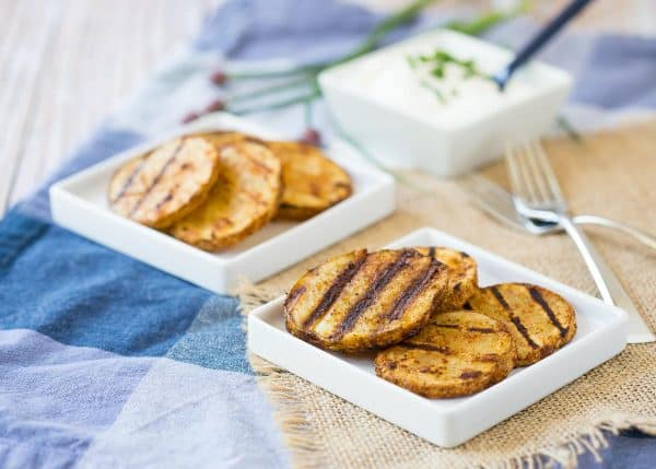 Grilled potato slices on small square white plates, along with forks and square dish of sour cream.