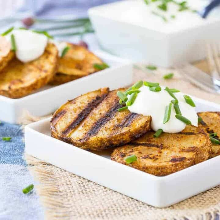 Grilled potatoes on square white plates, garnished with sour cream and chopped chives.