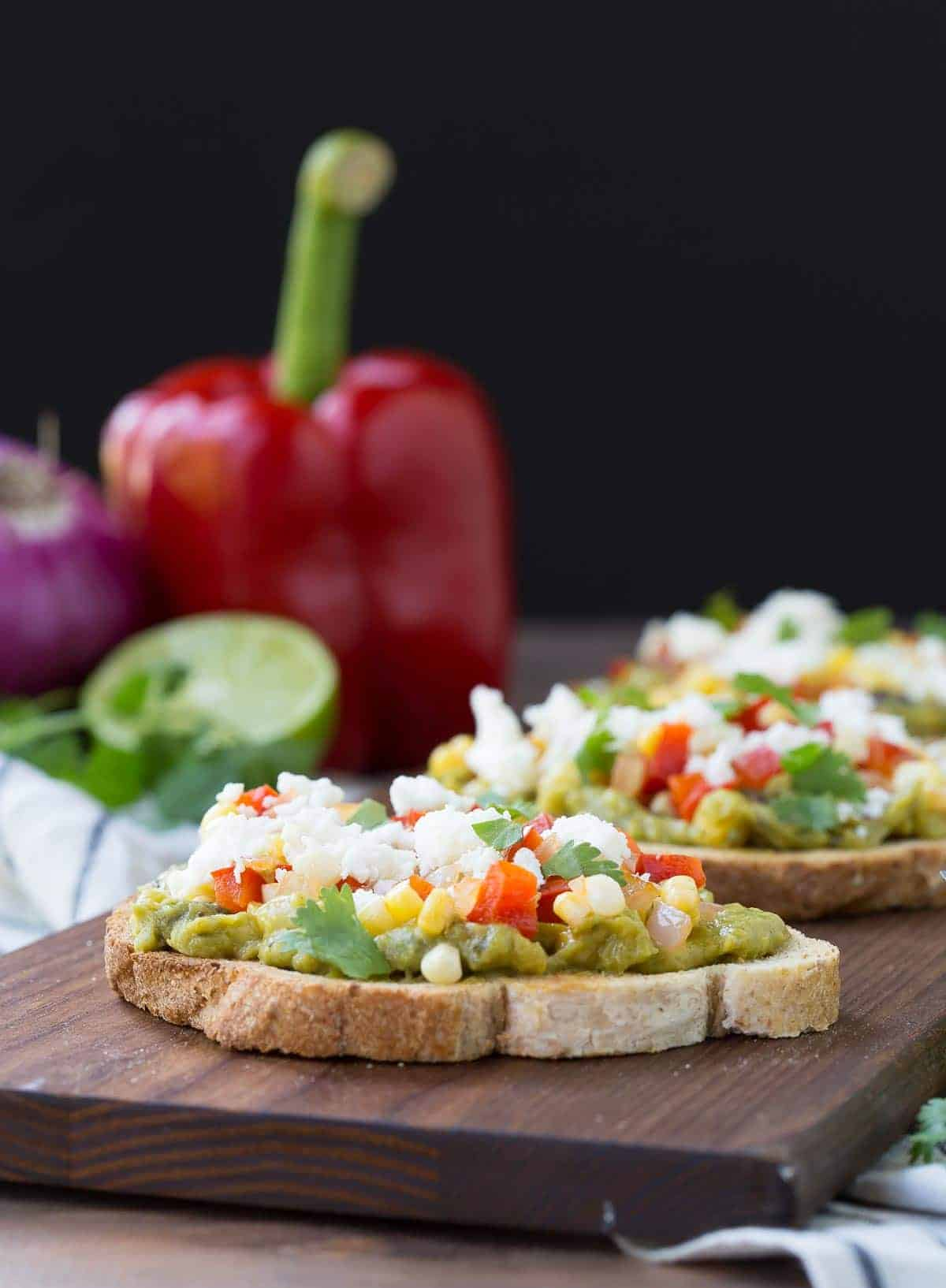 Front view of guacamole toasts on board with red onion, red bell pepper, half of lime, and cilantro along side.