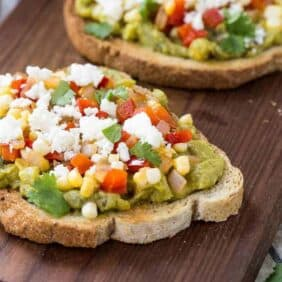 This southwestern guacamole toast is going to be your lunch go-to meal. It's easy to make, filling, and packed full of flavor thanks to peppers, sweet corn, lime, and cilantro. Get the avocado toast recipe on RachelCooks.com!