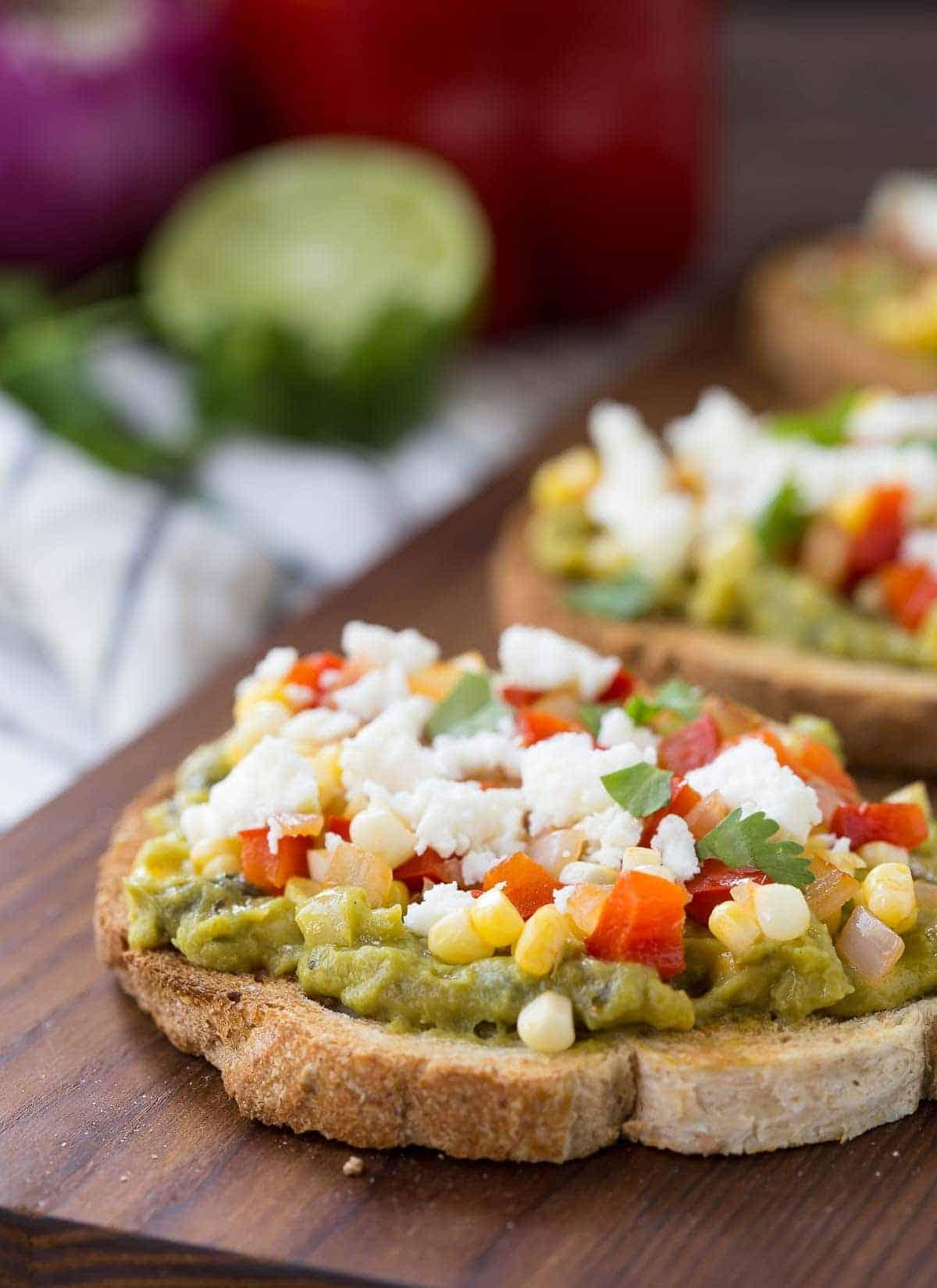Closeup of guacamole toast on wooden cutting board.