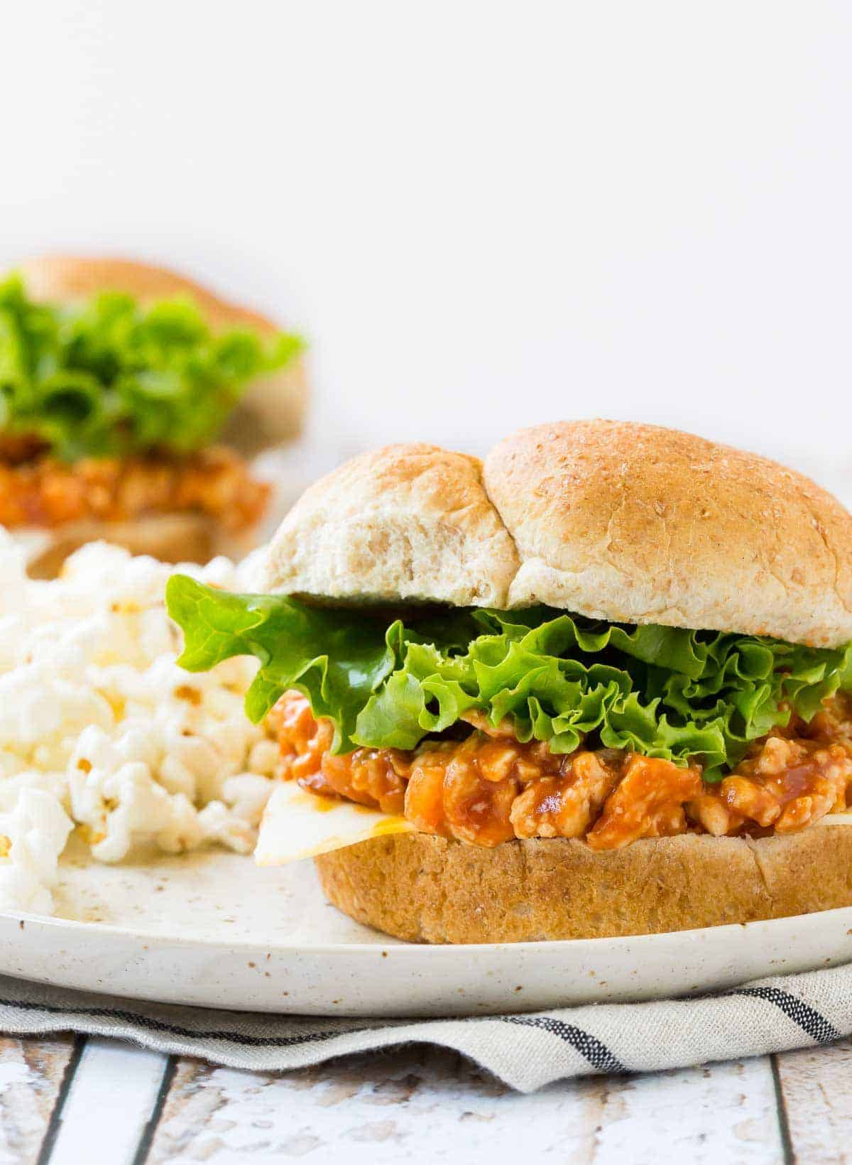 Sloppy Joe on bun with lettuce and cheese, on plate with popcorn.