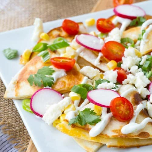 """How about we put the cheese inside the """"chips"""" and use quesadillas as the base for some summer-inspired quesadilla nachos? The result is incredible!"""