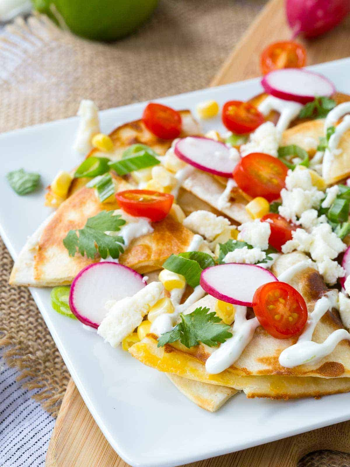 "How about we put the cheese inside the ""chips"" and use quesadillas as the base for some summer-inspired quesadilla nachos? The result is incredible!"