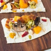 Experience a taste of fall with this ricotta flatbread! The party starts in the spiced ricotta and carries throughout the fun autumn toppings: bacon, squash, apples, mushrooms, and maple candied pepitas. You'll want to eat this all year! Get the easy recipe on RachelCooks.com!
