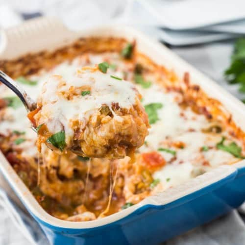 Baked casserole in blue baking dish, with spoon lifting out a serving.
