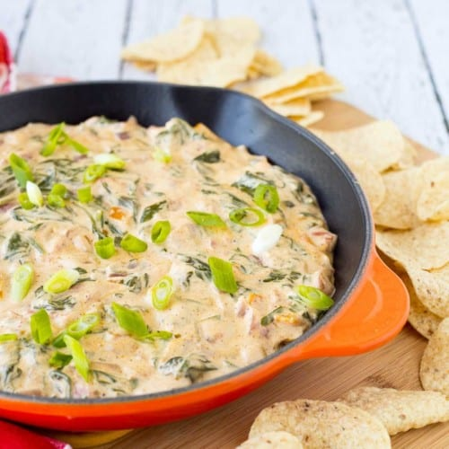 Mexican spinach dip in orange cast iron skillet surrounded by tortilla chips.