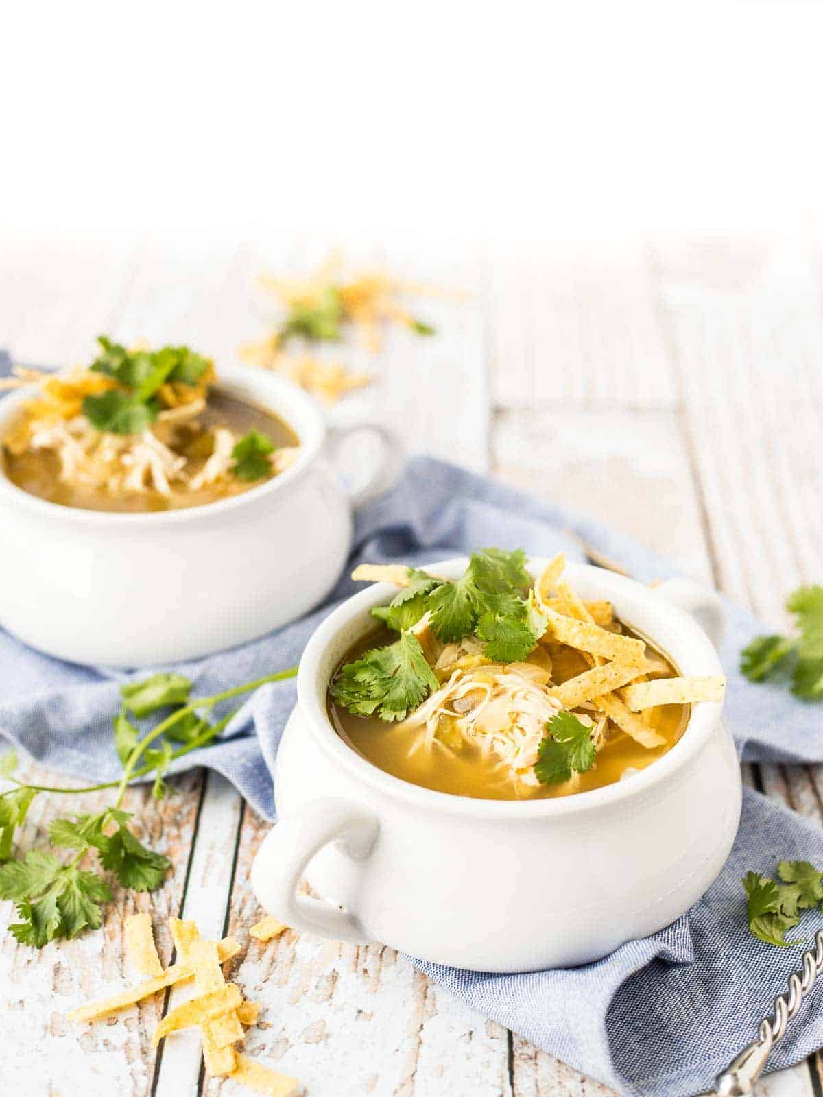 Chicken enchilada soup in white soup bowls with handles.