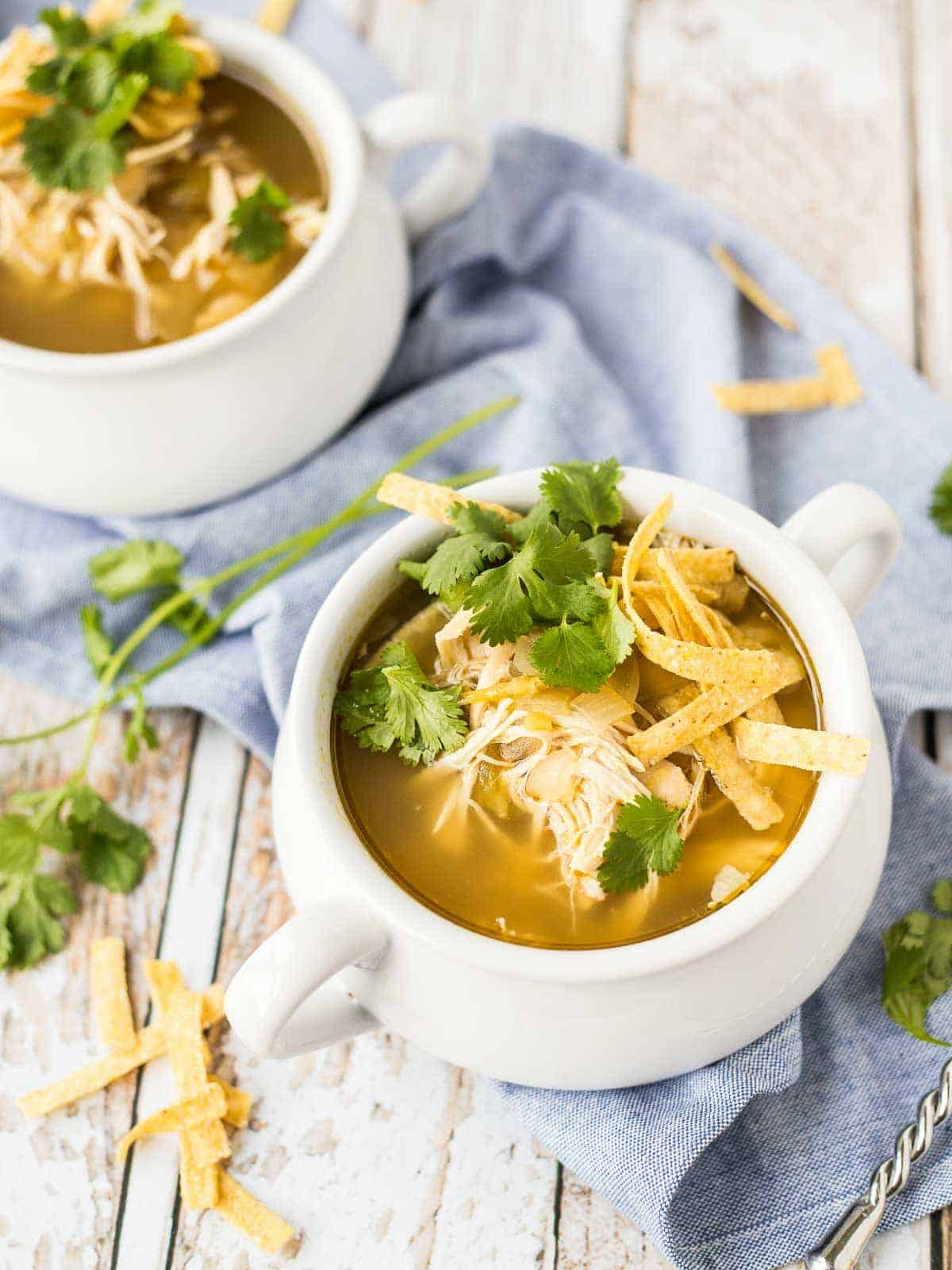 Overhead of soup in bowls, garnished with cilantro leaves, shredded cheese, and tortilla strips.