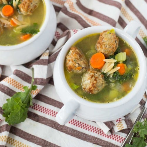Overhead of meatball soup served in white bowls.