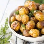 Partial image of roasted potatoes in round white serving dish, garnished with fresh dill.
