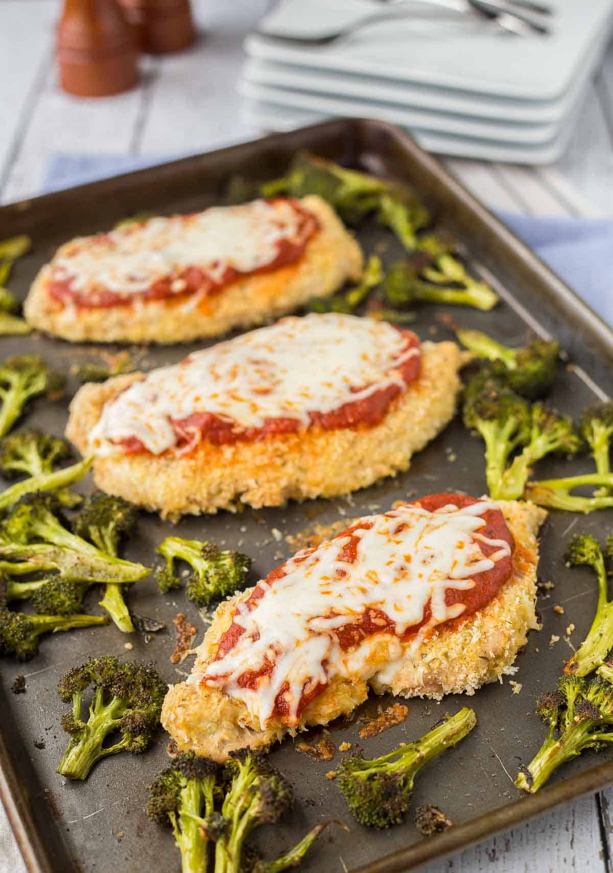Three chicken breasts on sheet pan with broccoli.
