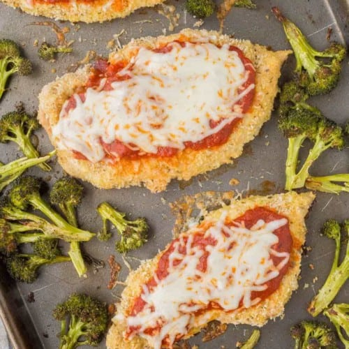 Overhead of chicken Parmesan with broccoli on sheet pan.