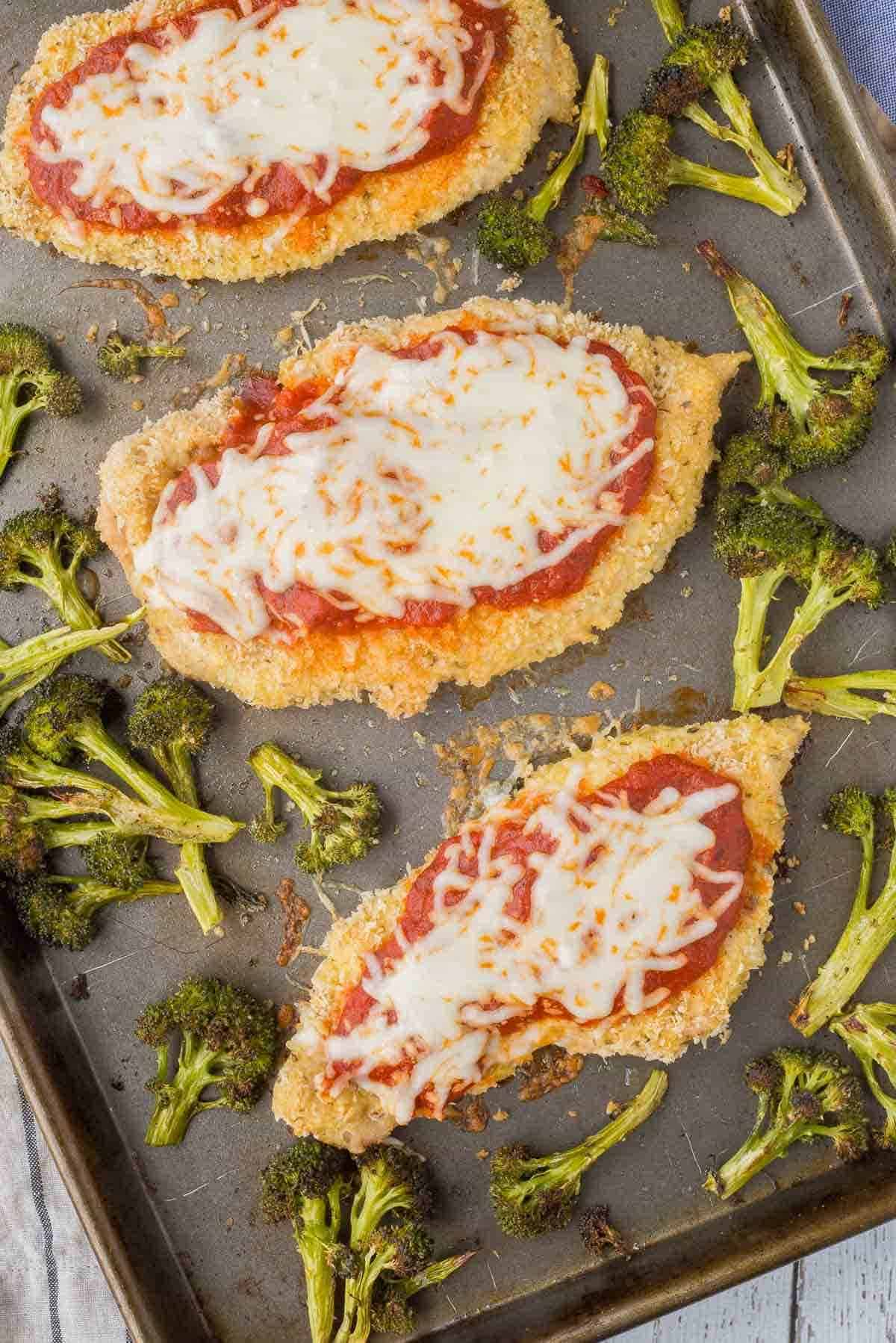 Overhead of chicken Parmesan and broccoli on sheet pan.
