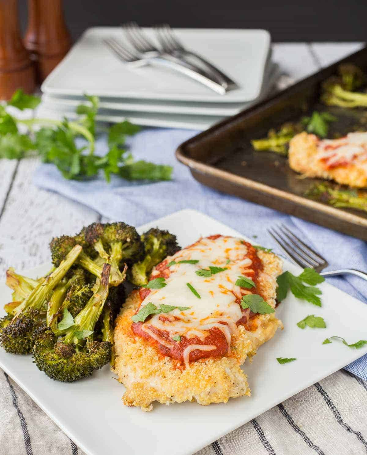 One serving of chicken Parmesan and broccoli on square white plate with fork.
