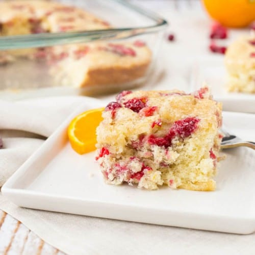 A serving of cranberry coffee cake on a square white plate with baking pan in background.