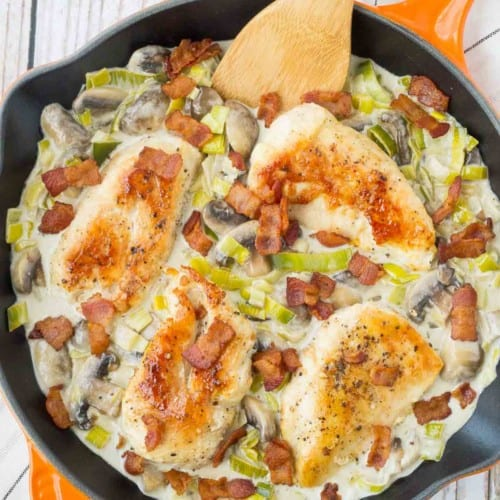 Overhead of chicken with sauce in orange skillet, garnished with bacon.