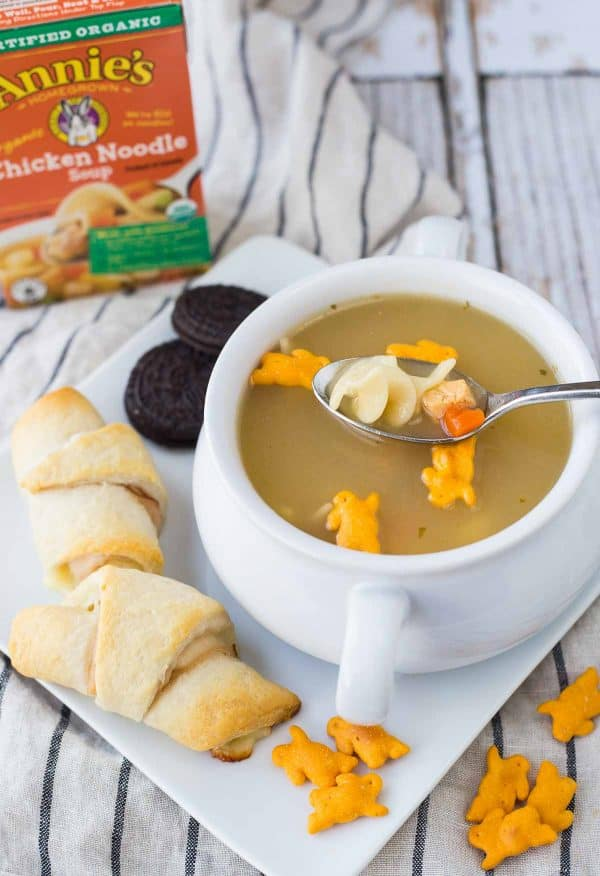 Soup garnished with bunny crackers, with spoon inserted.