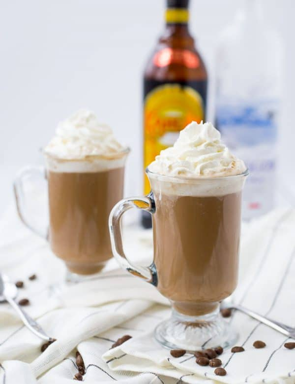 Footed clear glass mugs containing hot chocolate garnished with whipped cream, on white striped cloth, with bottle of Kahlua in background.